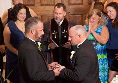 Aaron Huntsman (front L) and William Lee Jones (front R) complete their wedding vows, with Rev. Steve Torrence (C) officiating, on the steps of the Monroe County Courthouse in Key West, Florida, early January 6, 2015. The couple obtained the first same-sex marriage license issued in the Florida Keys. Same-sex marriage licenses were issued in the rest of the state starting just after midnight on Tuesday, when a stay expires on a ruling by U.S. District Judge Robert Hinkle in Tallahassee, who also struck down the ban approved by Florida voters in 2008. The legalization of gay marriage in Florida means about 70 percent of Americans now live in states permitting same-sex marriage, almost double the number a year ago, according to the Human Rights Campaign, a national advocacy group. REUTERS/Carol Tedesco/Florida Keys News Bureau/Handout via Reuters (UNITED STATES - Tags: POLITICS SOCIETY TPX IMAGES OF THE DAY) ATTENTION EDITORS - THIS PICTURE WAS PROVIDED BY A THIRD PARTY. FOR EDITORIAL USE ONLY. NOT FOR SALE FOR MARKETING OR ADVERTISING CAMPAIGNS. THIS PICTURE IS DISTRIBUTED EXACTLY AS RECEIVED BY REUTERS, AS A SERVICE TO CLIENTS. NO SALES. NO ARCHIVES